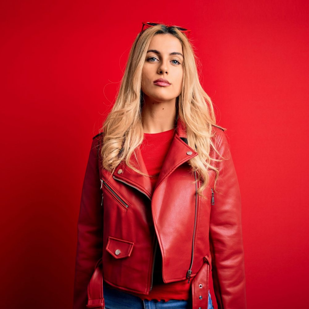Young beautiful blonde woman wearing casual jacket standing over isolated red background Relaxed with serious expression on face. Simple and natural looking at the camera.